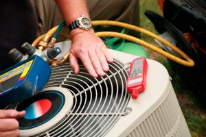 Technician's hand working on an air conditioner