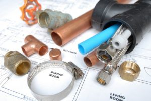 various plumbing components sitting on top of a home blueprint